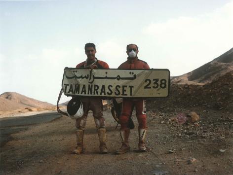 Luca e un suo amico mostrano un cartello con scritto Direzione Tamanrasset 238